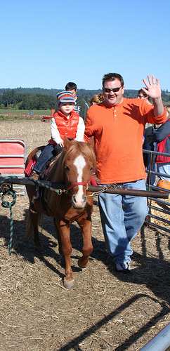 Photo of parent with child riding ponies at a pumpkin patch Fall Halloween fair.
